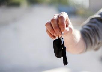 Hombre entregando sus llaves como señal de confianza con la aseguradora.