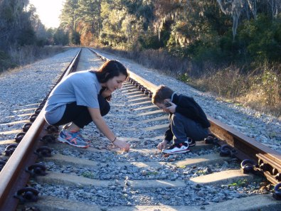 Two cousins sitting together on train tracks behind the sugar mill. They found a pinecone.