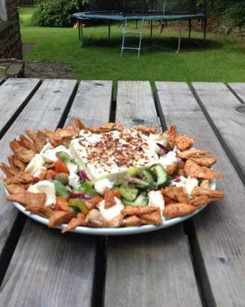 Quick Feta Salad with Paprika Pitta Chips on wooden table in garden
