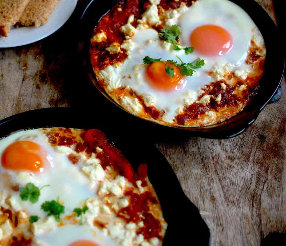 Two plates on eggs and feta in a tomato base