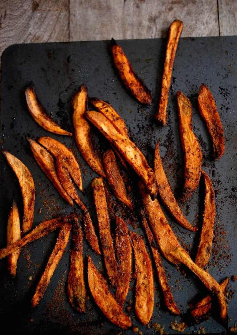 Sweet potato fries on a baking tray on a table
