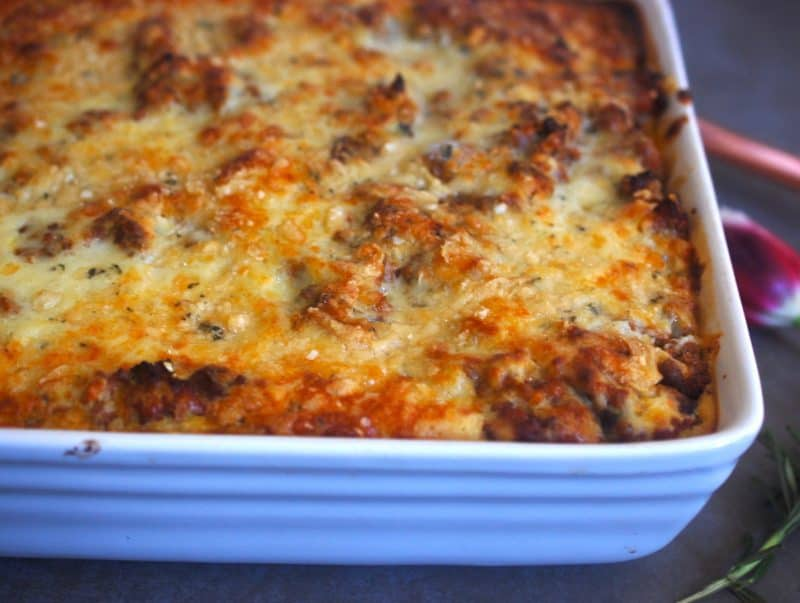 Moussaka in a white baking dish with spatula to side