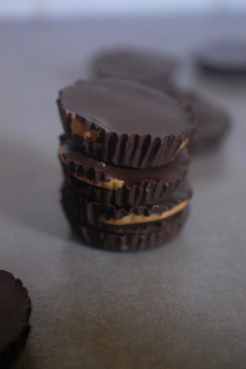 3 Chocolate Peanut butter cups piled on top of each other on grey background