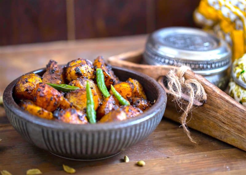 Tamarind and mustard seed potatoes in bowl on table