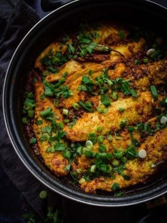 Masala Fish in a pan topped with spring onions and coriander
