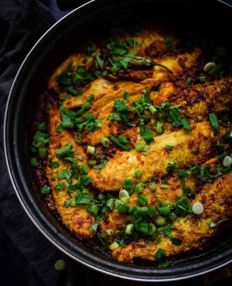 Fish in a Masala Sauce with Spring Onions and Coriander on top in a large pan