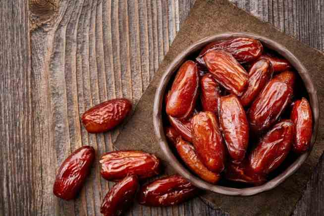 Dates in a round bowl on a wooden table