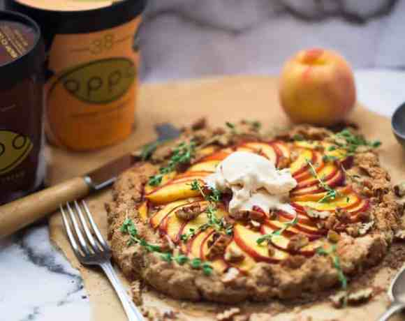 Wholewheat Peach Galette with Salted Caramel Ice Cream and Pecans on baking paper on a marble background with two tubs of oppo ice cream beside it