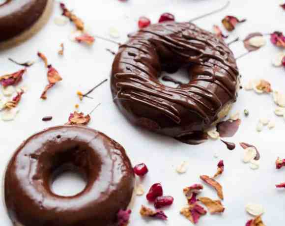 Chocolate glazed doughnuts on white background decorated with tiny petals and pomegranate