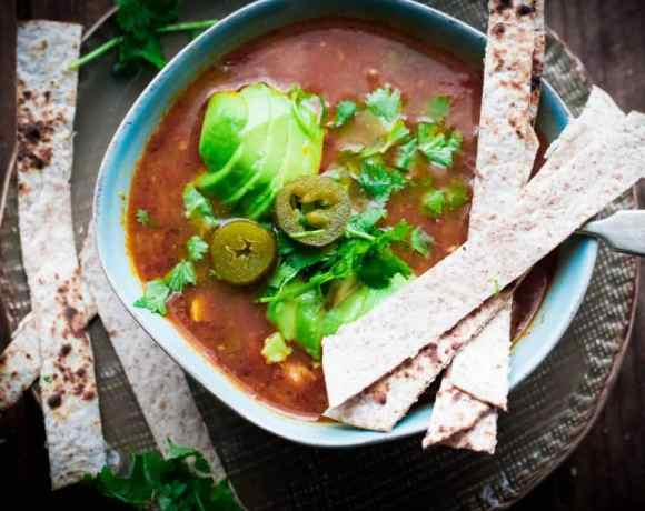 Chicken, Jalapeno and Lime Taco Soup in bowl with tortilla strips