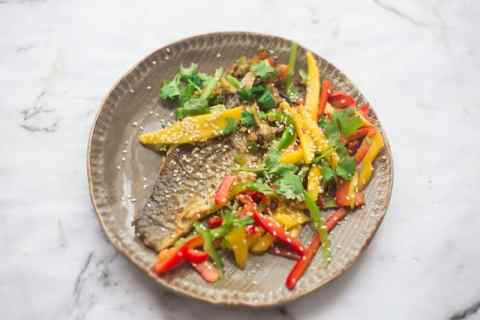 Thai Sea Bass with Mango and Pepper Salad covered in sesame seeds in a plate on a marble background.