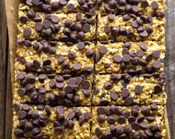 Peanut butter bars topped with choc chips on baking paper