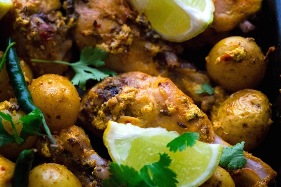 Roasted Chicken Legs with Baby Potatoes in indian spices with lemon slices. close up shot