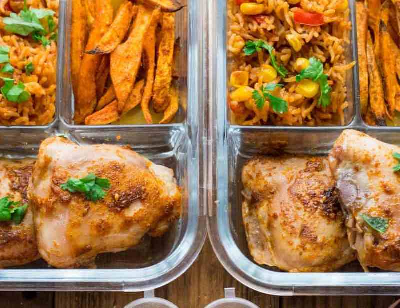 Three section glass container. filled with chicken sweet potato and veg rice on wooden board.