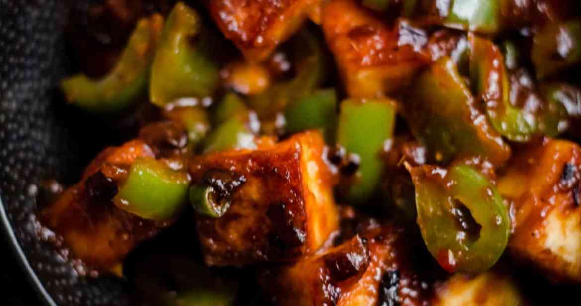 Chilli Paneer with peppers in a black bowl