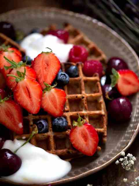 Waffles with fresh berries and yoghurt on plate
