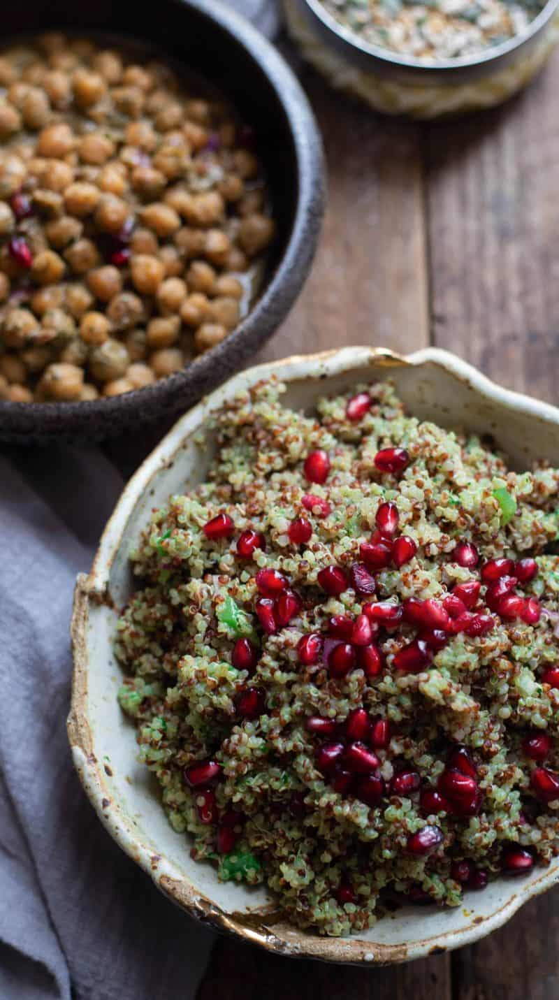 Quinoa topped with pomegranate with hand made bowl on a wooden board with a bowl of chickpeas.
