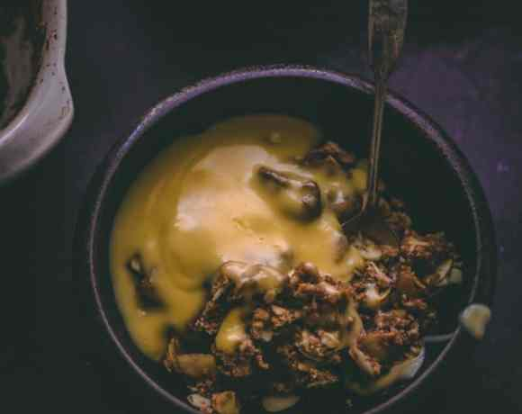 Spelt crumble in a dark bowl with thick custard