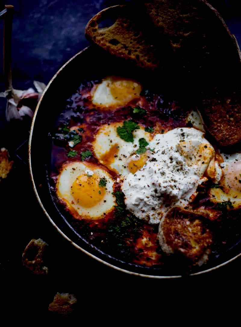Middle Eastern Shakshuka with Burrata and coriander in pan with toasted sourdough on top