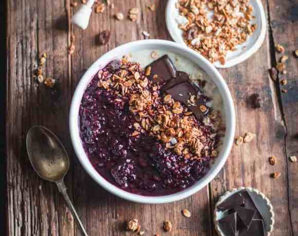 Oats with Blackberry and Cardamom Compote in a bowl with three small plates with raw ingredients on wooden board.