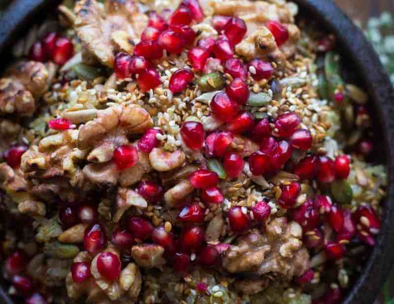 Quinoa salad with walnuts and pomegranate in a bowl with flowers in background
