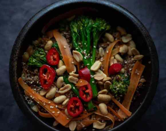 Quinoa with stir fry vegetables and peanuts in bowl on grey background