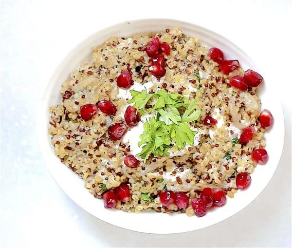 Quinoa and freekah topped with yoghurt and pomegranate in a white bowl on a white background.