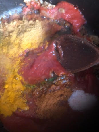 Spices and Passata in pot with wooden spoon