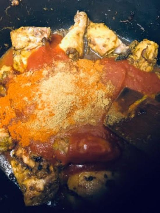Chicken and spices and tomato in large pot with wooden spatula, pre mixed