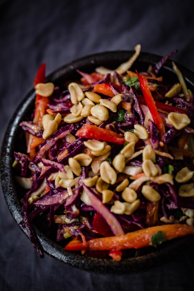 Red Cabbage, Red Pepper, Coriander and Peanuts in a black bowl on a grey creased towel