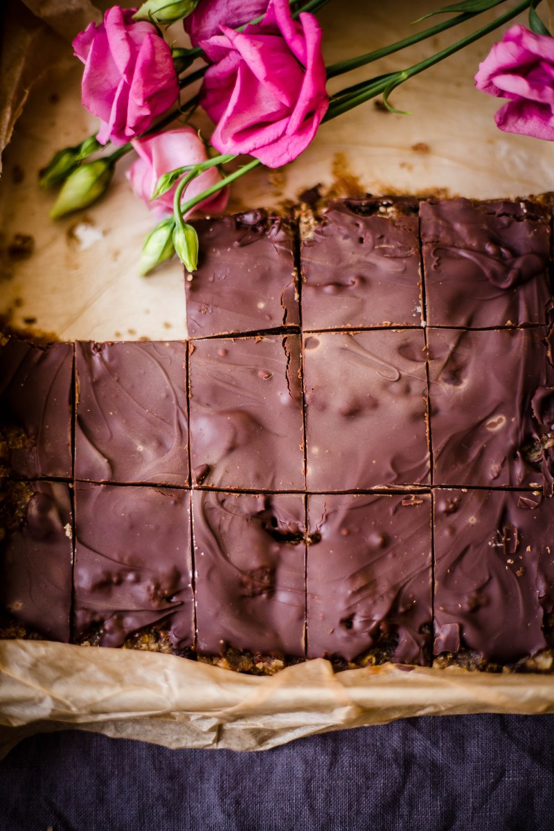 A half filled tray with greaseproof paper and chocolate covered date and honey bites with pink flowers in the tray at the back