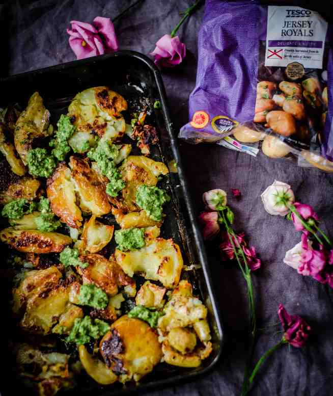smashed golden potatoes in a tray with green pesto over the top, jersey royal packet from tesco at side, flowers scattered around on grey towel