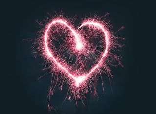 A sparkly pink heart on a dark background