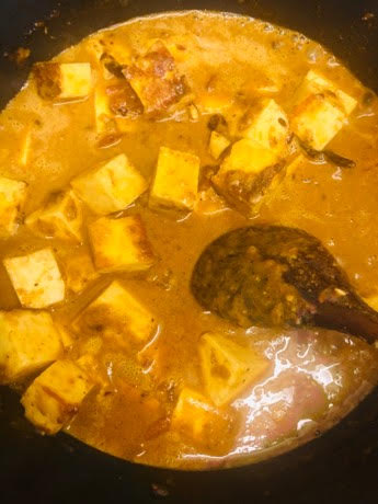 Paneer added to curry in pot