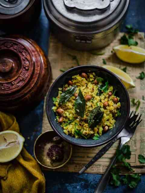Poha in a bowl with Nuts and curry leaves