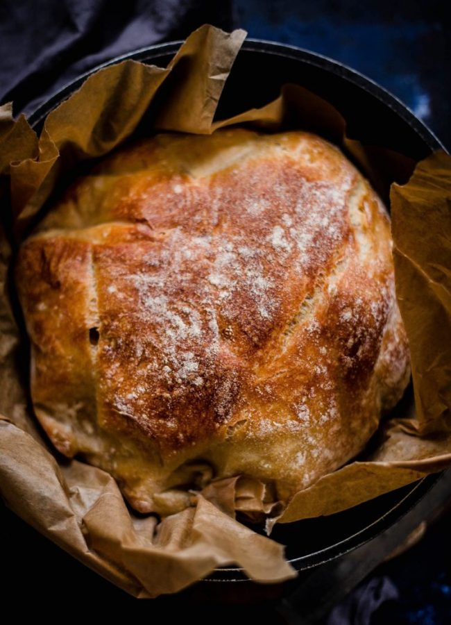Baked bread in a cast iron pot on baking paper