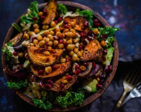 Kale salad with sweet potato , pomegranate and roast chickpeas in bowl