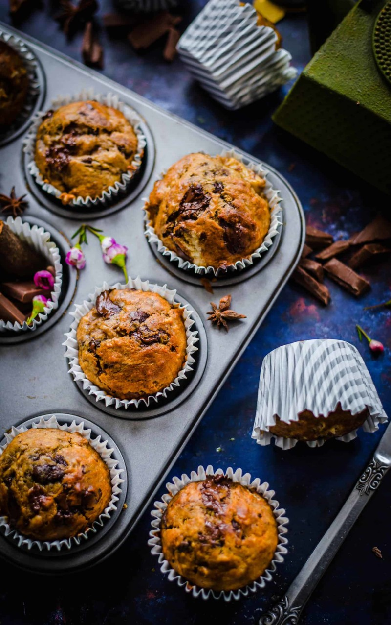 Banana and chocolate muffins in tin with spices scattered around