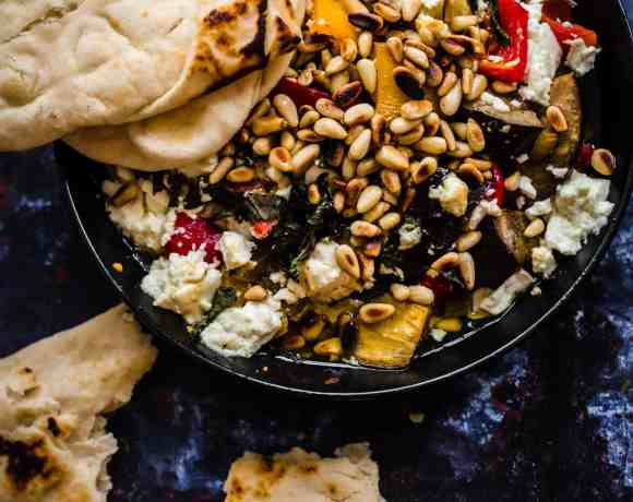 Roast veg with feta and pine nuts in bowl with flatbread to the side