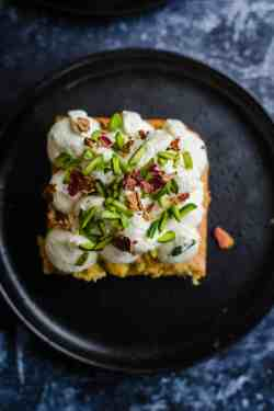 Ras Malai Milk Cake with rose petals and pistachios on black plate