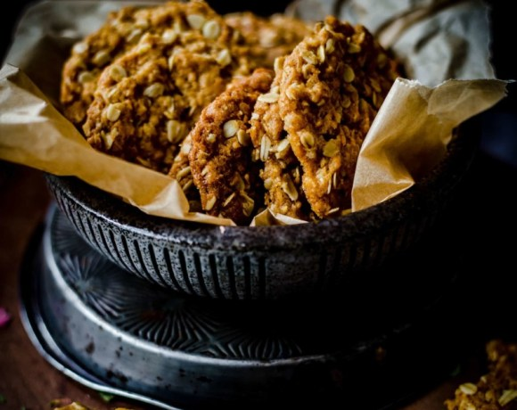 Anzac biscuits in a bowl with greaseproof paper