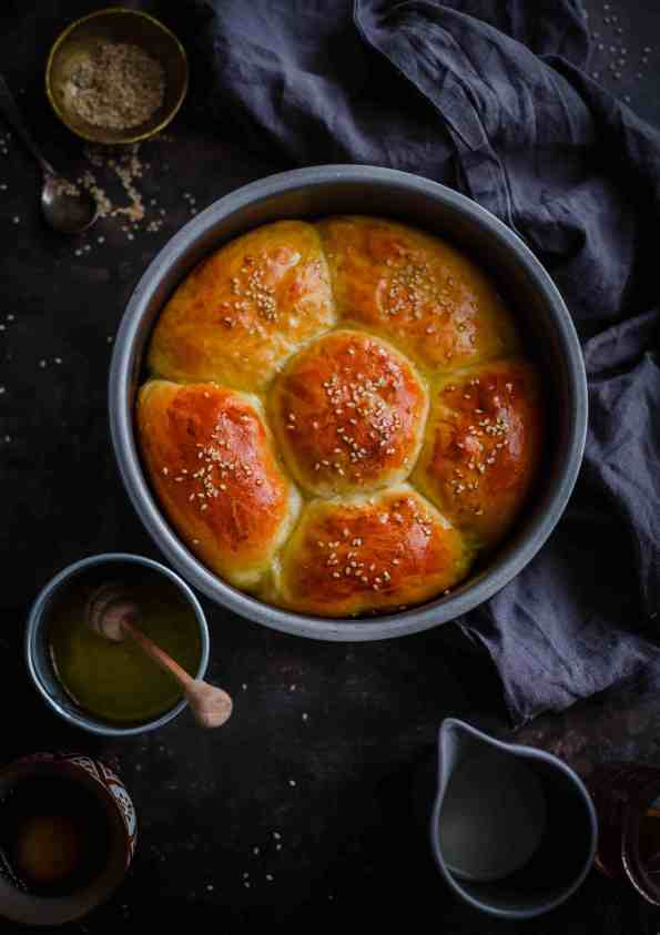 Chicken milk buns in flower shape in round tin with butter to side