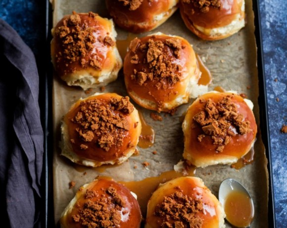8 Buns on a lined tray filled with cream, topped with caramel and crushed biscuits