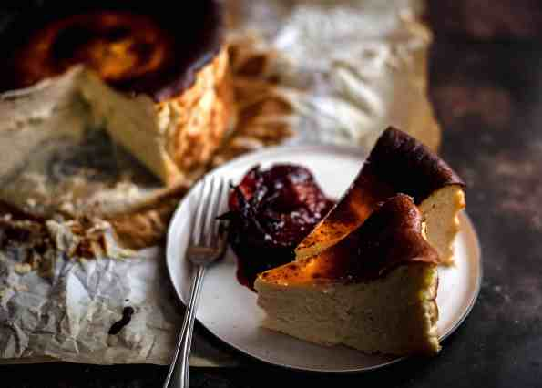 2 slices Basque burnt cheesecake on plate with poached plum and star anise