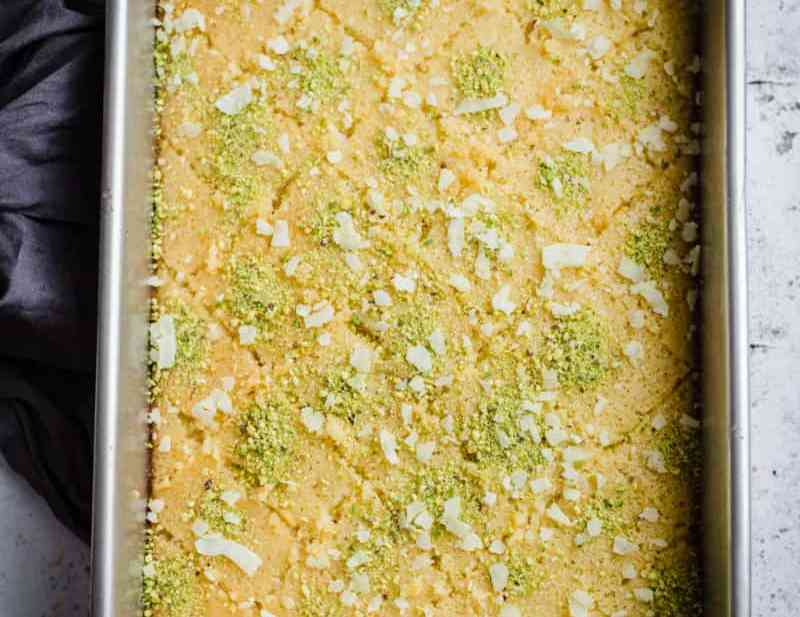 Revani in tray with pistachio and coconut topping