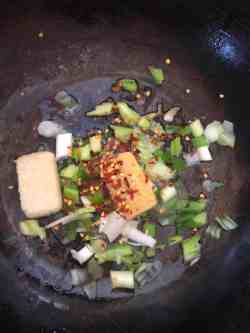 Oil, Spring Onions, Ginger, Garlic and red chilli flakes in wok