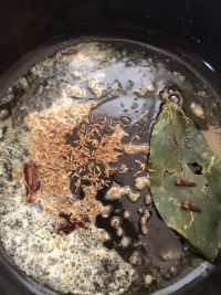 Cumin, Bay leaves and spices in pot with ghee