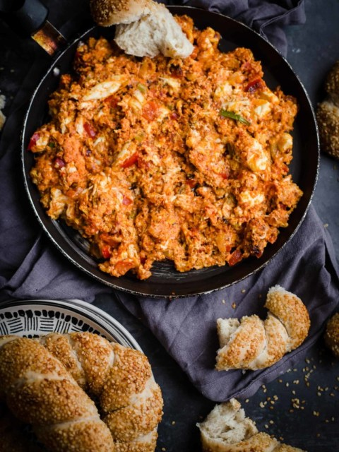 Menemen in a bowl with crusty bread to side