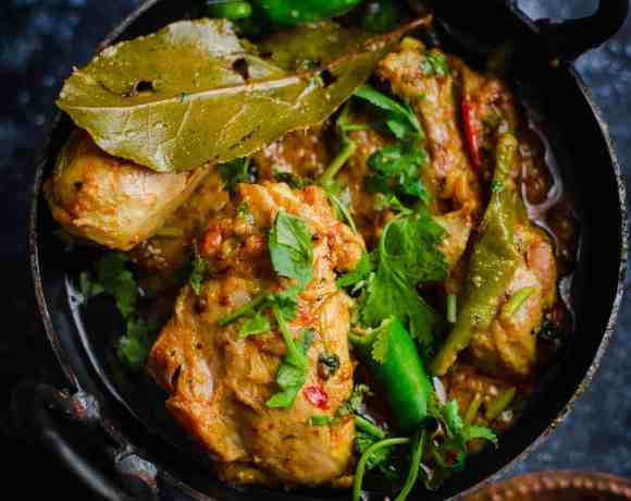 Karahi Chicken in wok with spices in plate to side