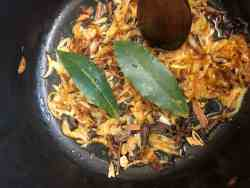 Bay leaves and whole spices added to caramelised onions